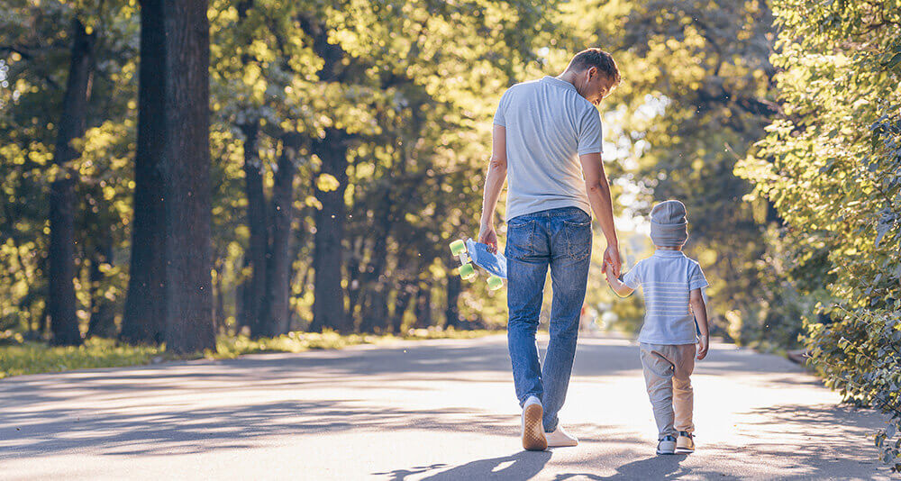 Father and son holding hands walk